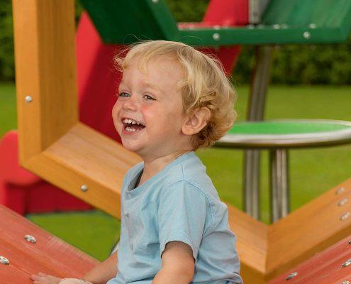 Tamino mit lachendem Kind auf einem Spielplatz